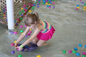 Child gathering Easter eggs in the pool